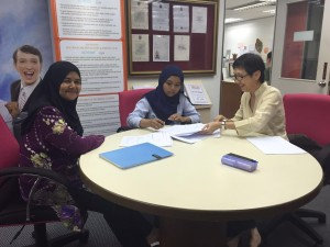 Nursyamimi and her mum signing the Scholarship Agreement